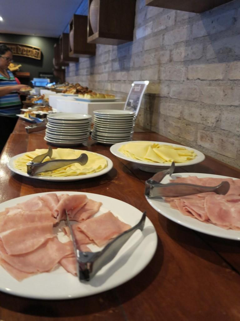 O café da manhã, muito bem servido, com vários tipos de medialunas.